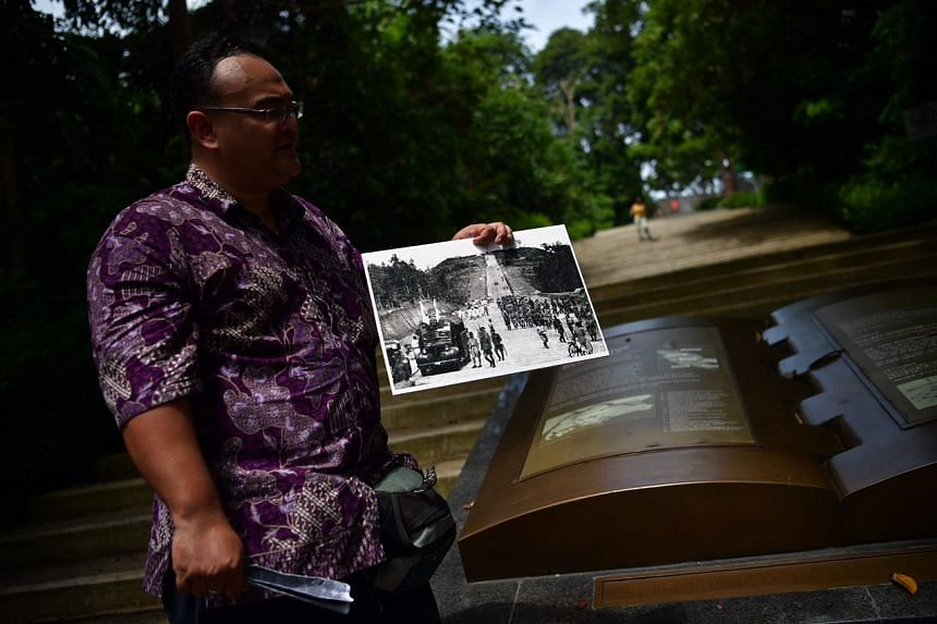 Dr Mohamed Effendy showing a picture of what the stairs to the Chureito Shrine looked like in the past. The shrine, which has since been destroyed, was built to honour Japanese soldiers who died at Bukit Timah.