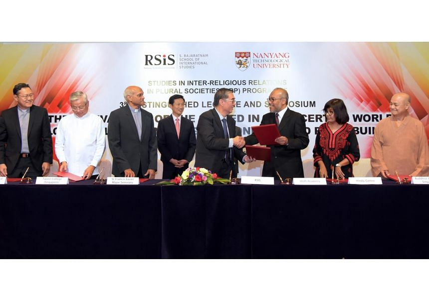 Minister Ong Ye Kung (centre) witnessing the signing of an MOU between RSIS and six religious institutions, at the Marina Mandarin Hotel on Feb 2, 2017.