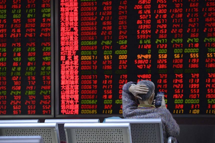 An investor uses a mobile phone to check stock indexes at a securities company in Beijing, China.