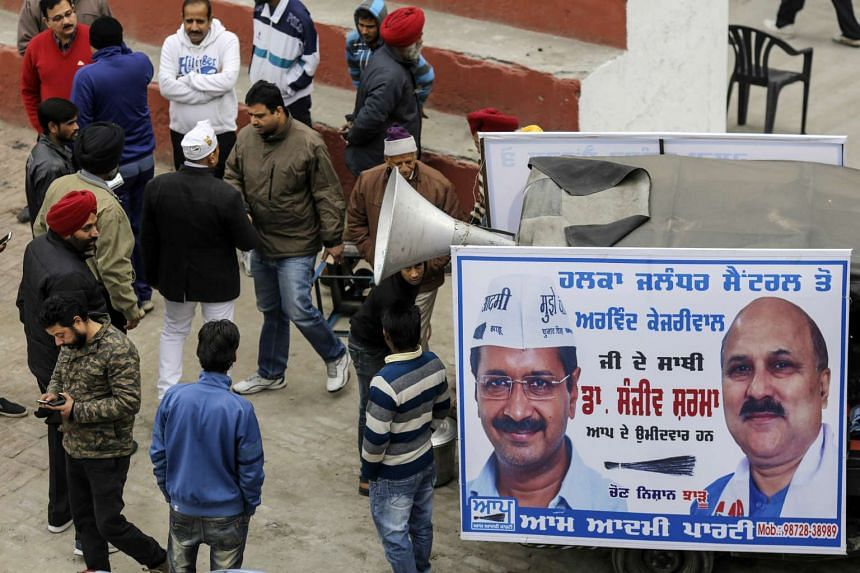 Supporters of the Aam Aadmi Party gathering near a banner featuring the image of AAP leader Arvind Kejriwal and AAP committee member Manish Sisodia, on Jan 21, 2017.