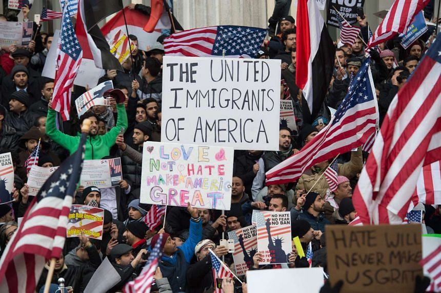 People waving flags and placards staging a protest against US President Donald Trump's executive order on immigration, in New York on Feb 2, 2017.