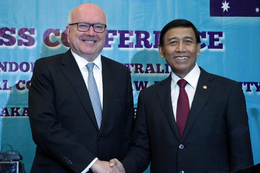 Indonesian Coordinating Minister for Political, Legal, and Security Affairs Wiranto (right) and Australian Attorney General Senator George Brandis pose for a photo during a press conference in Jakarta, Indonesia on Feb 2, 2017.