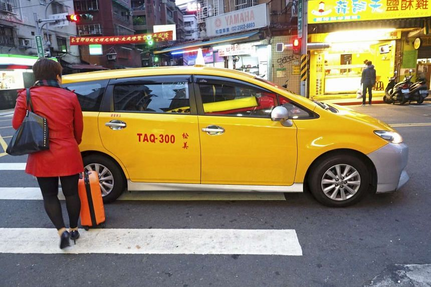 A woman carries her suitcase to get into a taxi in Taipei, Taiwan on Feb 2, 2017.