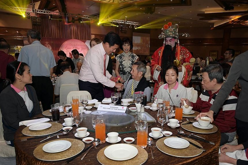Minister Ong giving a hongbao to a resident of the Sunshine Welfare Action Mission at the Singapore Maritime Officers' Union's annual Chinese New Year luncheon. To Mr Ong's left is the union's general secretary, Ms Mary Liew.