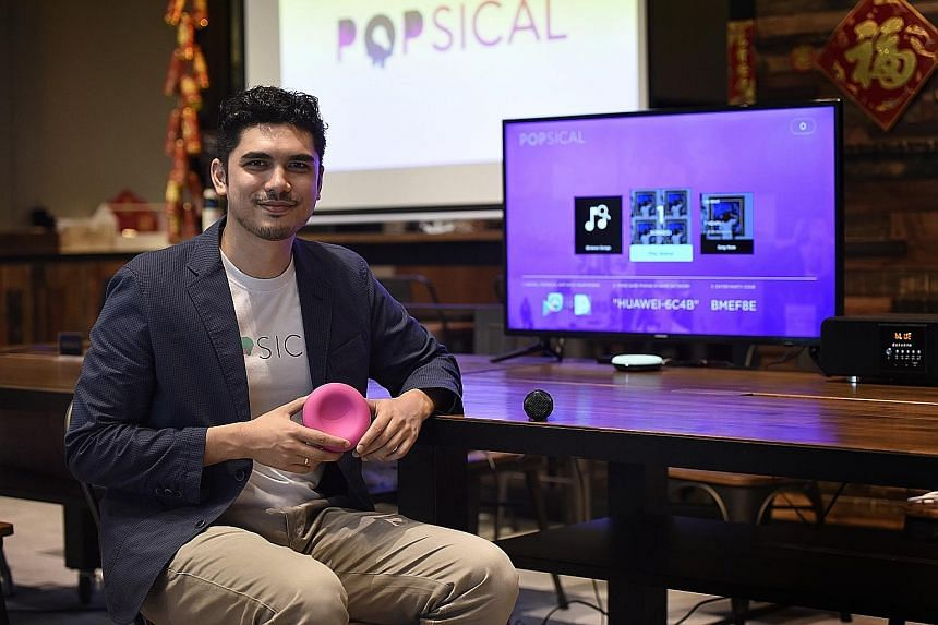 Mr Faruq Marican with Popsical, a portable karaoke system which can be plugged into any television set for a karaoke-on- demand experience.