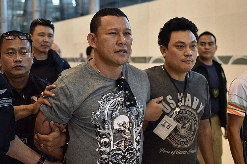 Xaysana (left) being escorted by police after his arrest at Suvarnabhumi Airport on Jan 19.