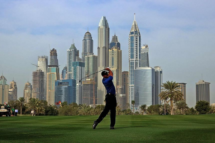 Tiger Woods playing a shot during the Dubai Desert Classic at the Emirates Golf Club. While 12 shots behind early leader Sergio Garcia, he hopes the wind blows his way for a good second round to make the cut.