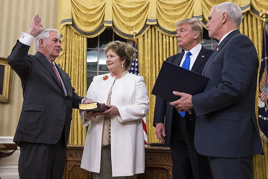 Mr Tillerson, seen here with his wife Renda St Clair, being sworn in as Secretary of State by President Trump and Vice- President Mike Pence in the Oval Office of the White House in Washington on Wednesday.