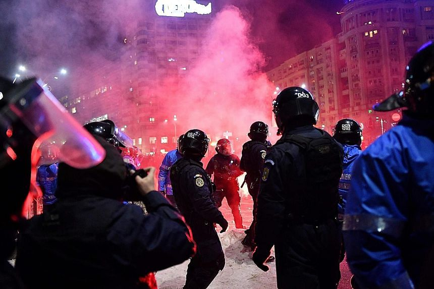 Riot police clashing with protesters in front of the government headquarters in Bucharest on Wednesday. The demonstrators were against a decree that could benefit dozens of corrupt officials.