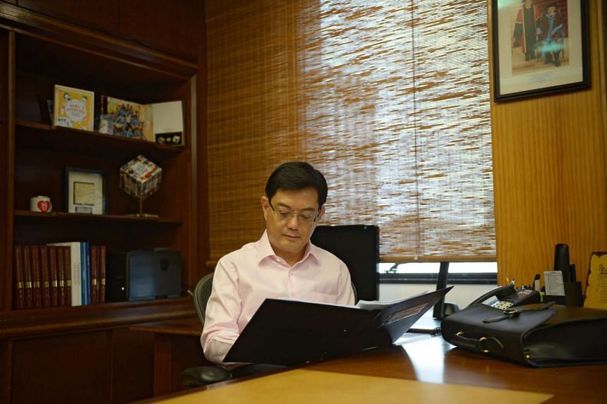 Finance Minister Heng Swee Keat prepares his documents at his office before making his first Budget speech in Parliament on March 24, 2016.