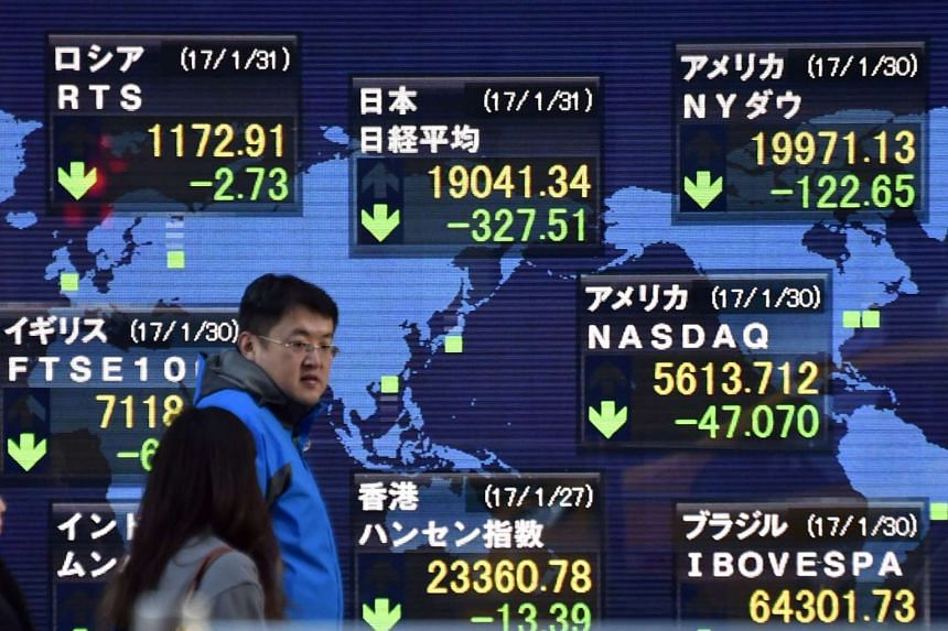 Pedestrians walk in front of an electric quotation board flashing share prices of the world, including the Nikkei key index of the Tokyo Stock Exchange, in Tokyo on Jan 31, 2017.