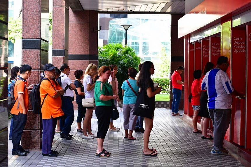 People depositing money at cash deposit machines outside OCBC Tampines Branch around 9am.