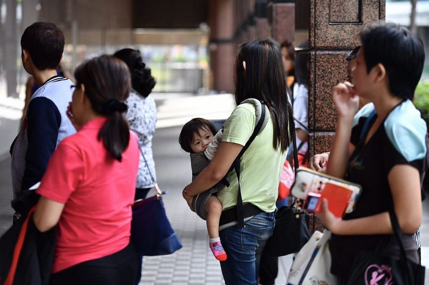 Ms Shirley Khoo, (in green) 42, self-employed, queueing with her 13-month-old daughter outside OCBC Tampines branch at 9.24am.