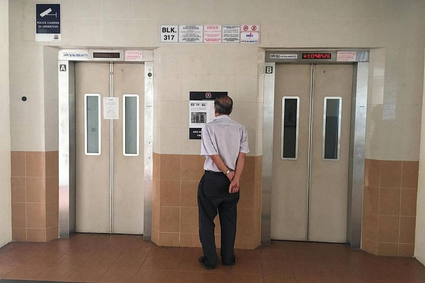 A man reads a Straits Times article pasted at the lift lobby of Blk 317 Ang Mo Kio Street 31.