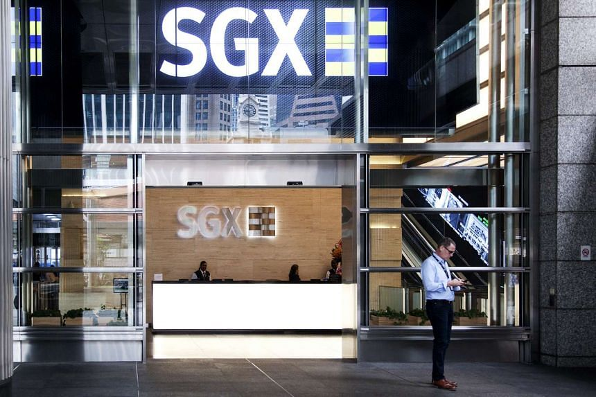 A man checks his phone at the entrance of the Singapore Exchange Ltd. (SGX) headquarters in Singapore.