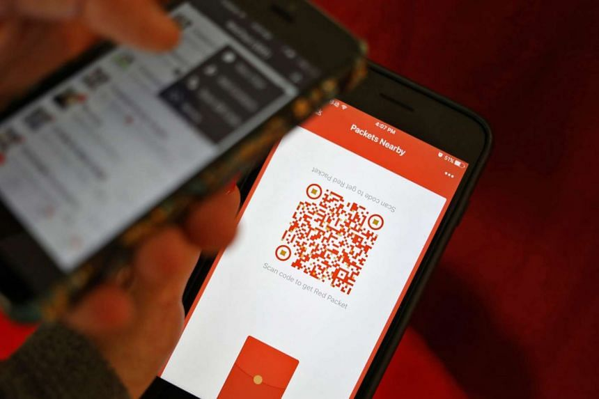 A photo illustration of a WeChat user scanning a QR code to retrieve a digital red envelope on the WeChat app.