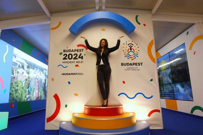 A hostess poses with Hungary's Olympic logo at a promotional spot as the Hungarian capital bids for the 2024 Olympic Games, in central Budapest, Hungary on Jan 31, 2017.