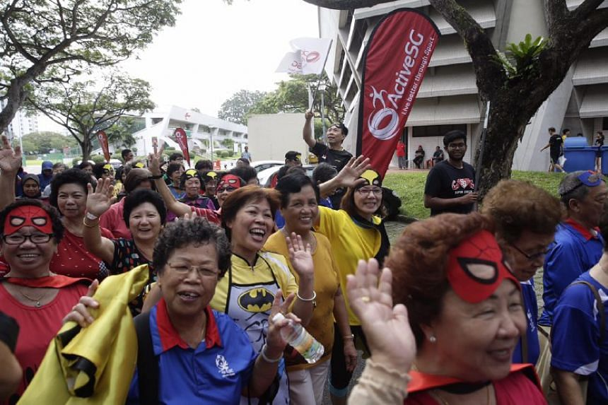 Member of Parliament for East Coast GRC Lee Yi Shyan, donning a Batman cape, flagging senior citizens off on a walkathon around the sports complex during the ActiveSG/ITE College Central Super Seniors Event at ActiveSG Sports Centre on Saturday (Feb