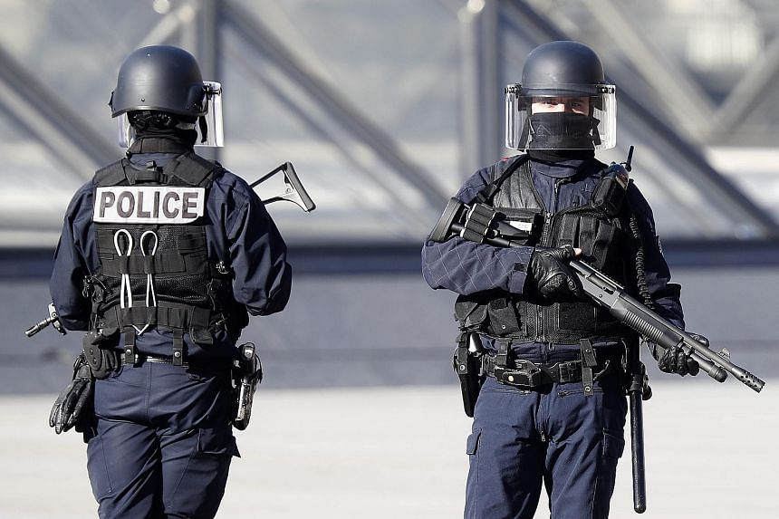 """Police officers standing guard near the Pyramid of the Louvre museum yesterday. Prime Minister Cazeneuve called the attack """"terrorist in nature"""", while a second man whose behaviour was """"suspicious"""" has been arrested."""