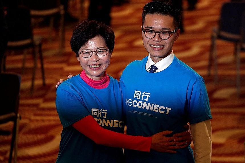 Mrs Lam with her son Jeremy at a Hong Kong election campaign event yesterday. She is widely seen as Beijing's preferred candidate and faces competition from former financial secretary John Tsang, among others.