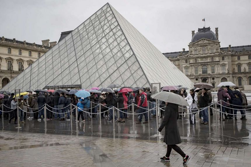 Tourists queue in the rain at the entrance of the Pyramid of Le Louvre Museum on Feb 4, 2017.