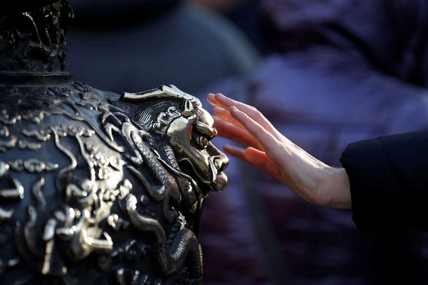 A woman touches a statue of a dragon for good fortune on the fifth day of the Chinese New Year at Baiyun Temple in Beijing, China, Feb 1, 2017.