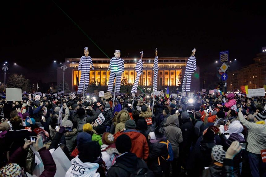 People hold effigies of politicians in prison clothing during a protest in front of government headquarters in Bucharest, Feb 3, 2017.