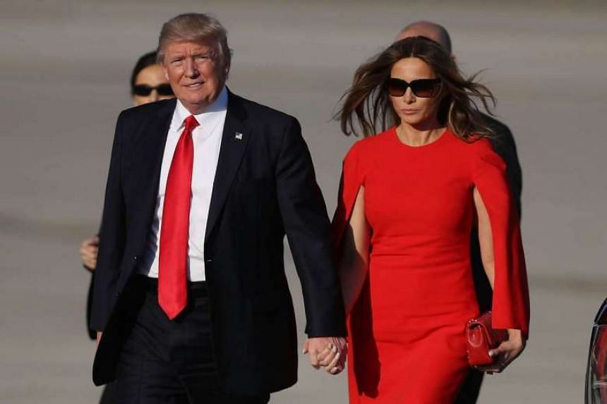 Trump walks with his wife Melania after arriving aboard Air Force One in Florida for a three-night getaway.