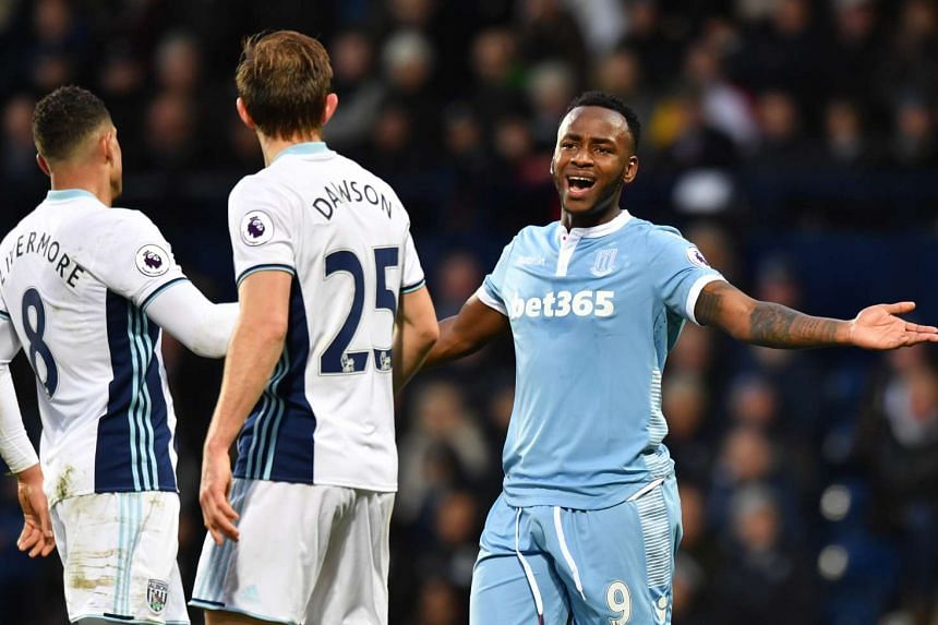Stoke's Saido Berahino clashes with West Bromwich Albion's Jake Livermore and Craig Dawson.