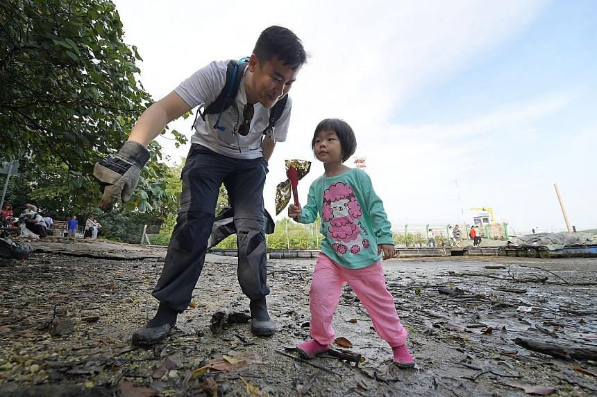 "Programme manager Adrian Lim and his daughter Elizabeth were among the 67 volunteers cleaning up the Lim Chu Kang mangrove yesterday (below). ""People should know that there's all this nature right in our backyard, but there's also all this trash,"" sa"