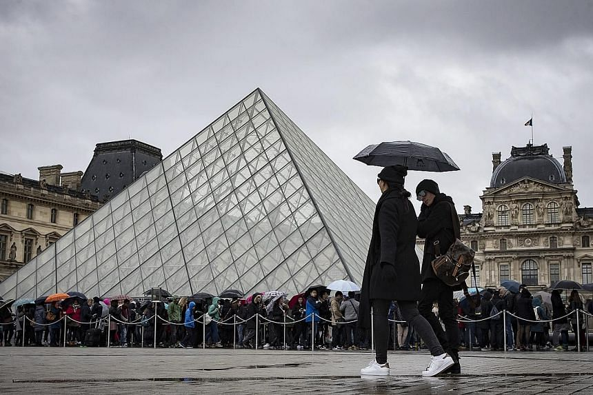 Tourists queueing in the rain at the entrance of the Louvre in Paris yesterday, a day after a soldier shot an attacker at the museum.