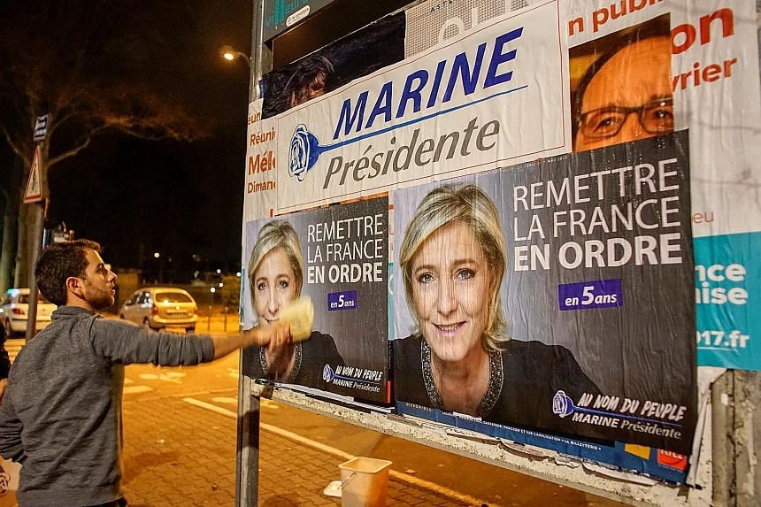 NF members putting up posters of Ms Le Pen, ahead of her rally in Lyon yesterday to spell out her platform for the French presidential polls starting in April.