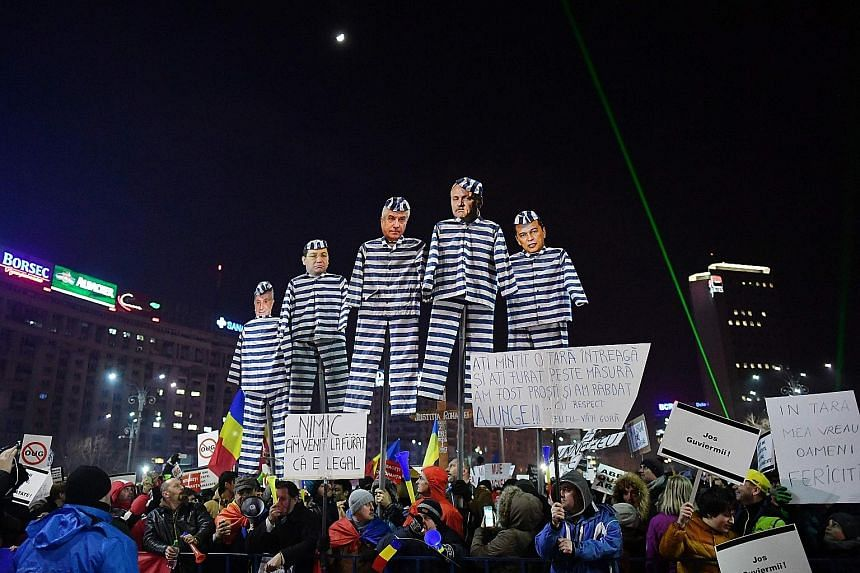 People holding cardboard cut-outs of figures from the ruling Social Democrats during a protest on Friday in front of the government headquarters in Bucharest, against the controversial decree that will decriminalise abuse-of-power offences involving