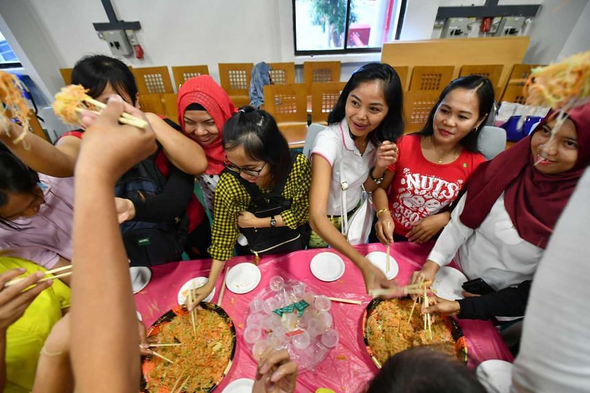 Foreign domestic workers take part in lo hei during the Chinese New Year celebration at Fast Befriender Club House on Feb 5, 2017.