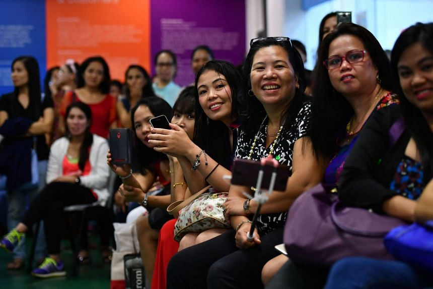 Foreign domestic workers  watch a performance during the Chinese New Year celebration at Fast Befriender Club House on Feb 5, 2017.
