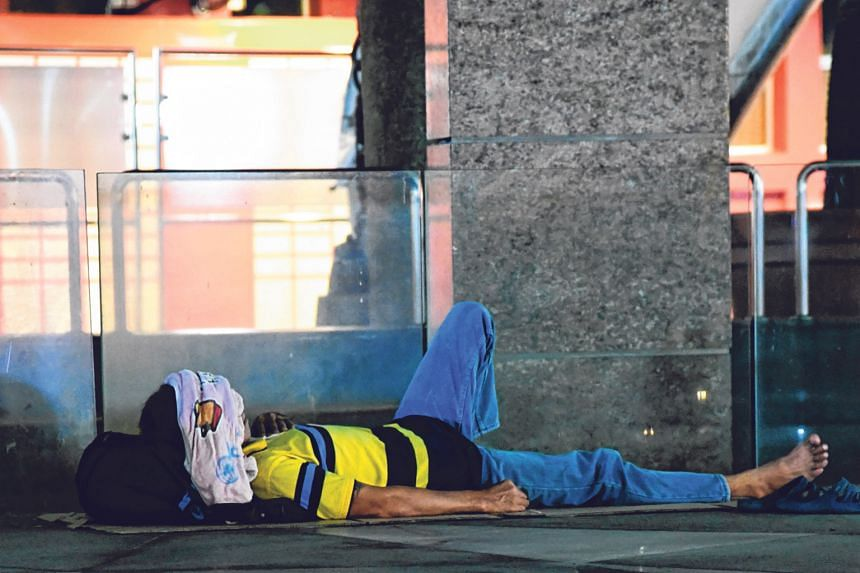 THEN: A bare strip of discarded cardboard serving as this man's makeshift mattress as he stretches out along a street in Toa Payoh to grab some shut-eye. Fewer homeless families are being picked up by the authorities.