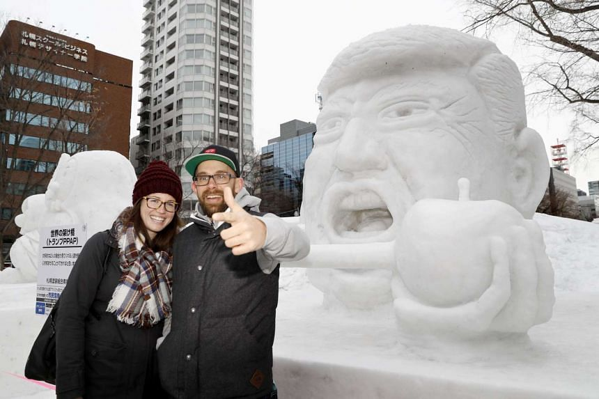 Tourists pose for a photograph in front of a snow statue of US President Donald Trump during the Snow Festival in Sapporo on Feb 6, 2017.