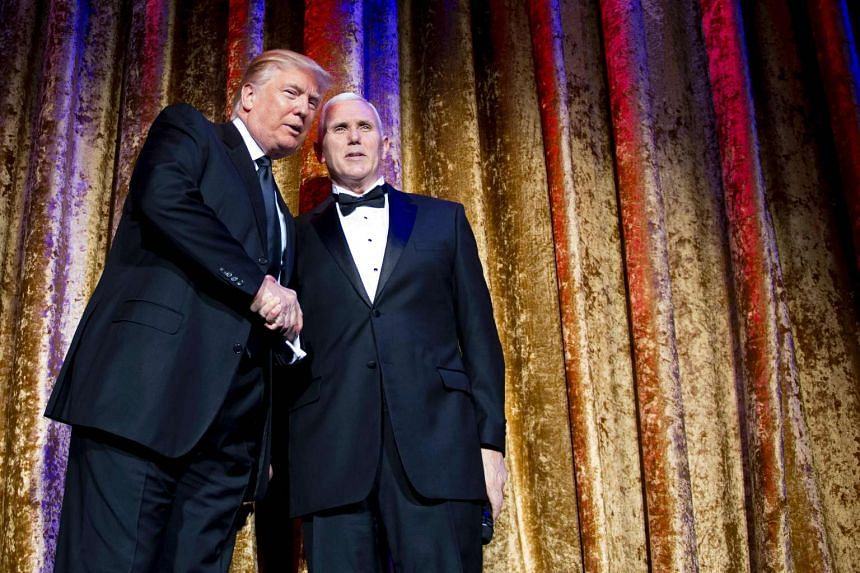 US President-elect Donald Trump (left) shakes hands with Vice President-elect Mike Pence (right) as they attend the Chairman's Global Dinner in Washington, DC on Jan 17, 2017.