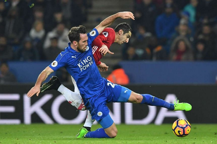 Leicester City's Austrian defender Christian Fuchs vies with Manchester United's Armenian midfielder Henrikh Mkhitaryan (right) during the English Premier League football match in Leicester, central England on Feb 5, 2017.