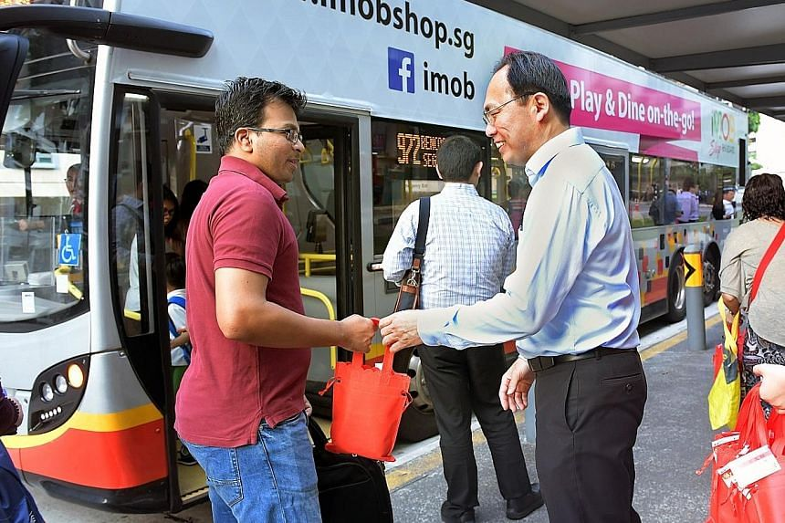 Mr Liang giving out goodie bags at the Block 458 Segar Road bus stop last Friday morning. He uses the opportunity to ask about the reliability of bus services in his ward, under an initiative called Happy Bus Stops @ Zhenghua.