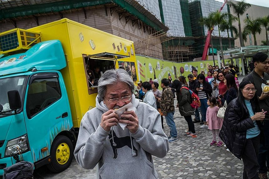 Is HK$20 (S$3.60) for one pineapple bun (bo lo bao) overpriced? Hong Kong chief executive contender John Tsang (left) thinks so. Accompanied by his wife Lynn, the former financial secretary visited a newly opened food truck in Tsim Sha Tsui on Saturd