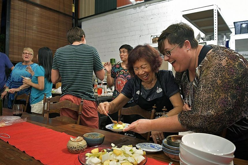 Madam Ng serving Ms Andrea Bork local food last Friday. Ms Bork, who was visiting from the United States, came to One Kind House with her mother and brother to learn how to make local dishes.