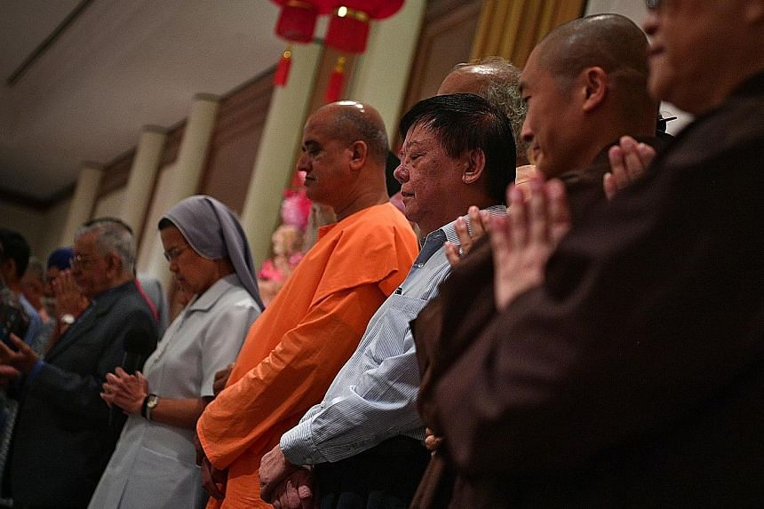 Representatives from the Inter-Religious Organisation (left) praying together at the Inter-faith Chinese New Year Reunion yesterday. The set of books (below), to be made available to religious institutions, is not for sale.