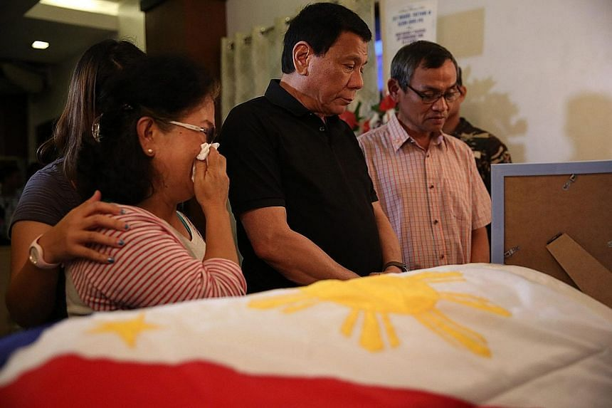 Mr Duterte with the family of Second-Lieutenant Miguel Victor Alejo at the soldier's wake last Saturday, after he was killed by the NPA. Mr Duterte has condemned the insurgents for resuming hostilities.
