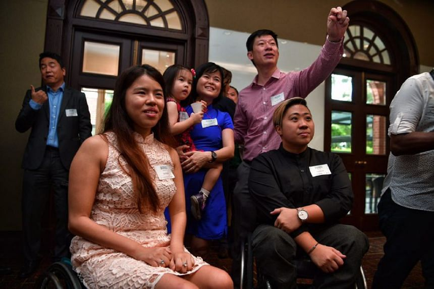 Paralympians Yip Pin Xiu and Theresa Goh takes pictures with Dr Chi Wei Ming and his family at the UBS Business University on Feb 6, 2017.