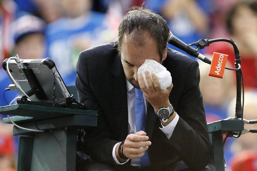 Umpire Arnaud Gabas holding an ice pack to his eye after being struck by a ball.
