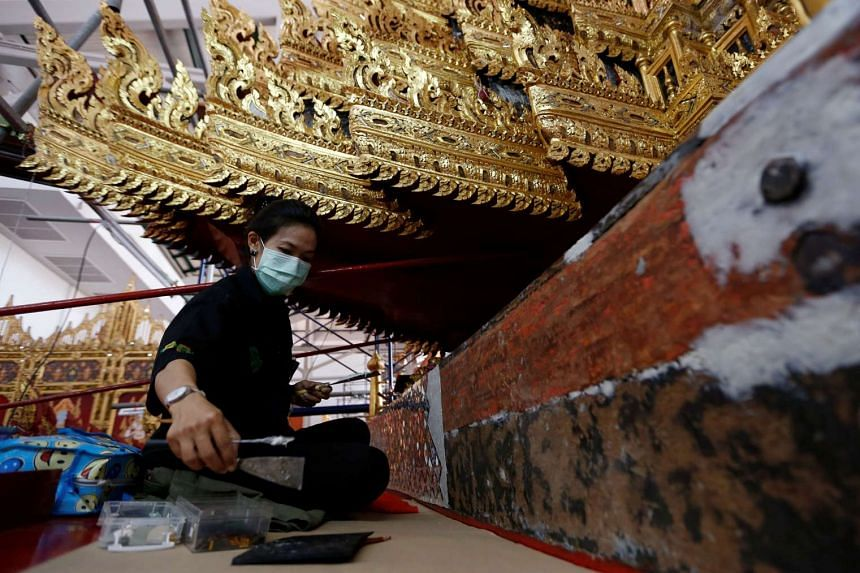 A worker from the National Museum of Thailand repairing the Royal Chariot.