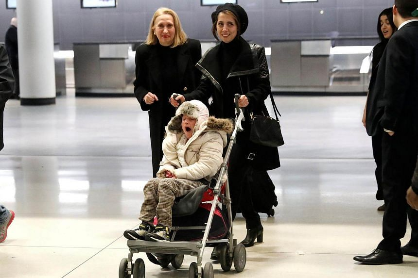 Twelve-year-old Alma Kashkooli, who has a severe medical condition, is wheeled out of customs by her mother Farimeh Kashkooli at John F. Kennedy International Airport in New York.