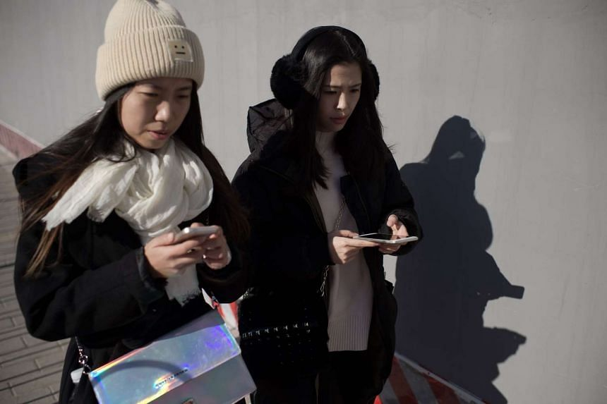 Two young women walk holding their smartphone in Beijing, on Dec 9, 2016.