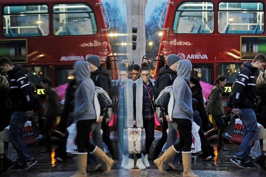 Shoppers are reflected in a shop window as they walk along Oxford Street in London.